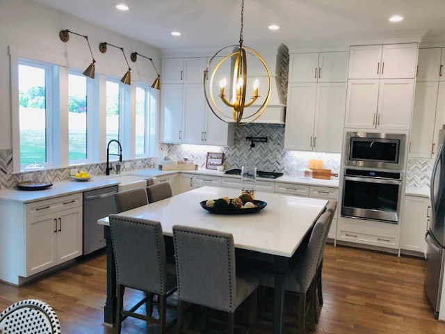 Shot of Milton model kitchen with hardwoods, white countertops, white cabinets, and interesting tile backsplach.