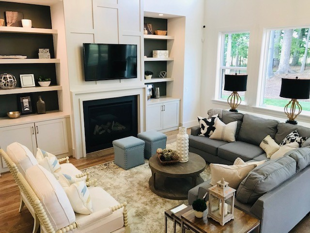 white judges panel fireplace flanked by built in bookshelves in cozy living room of Milton model